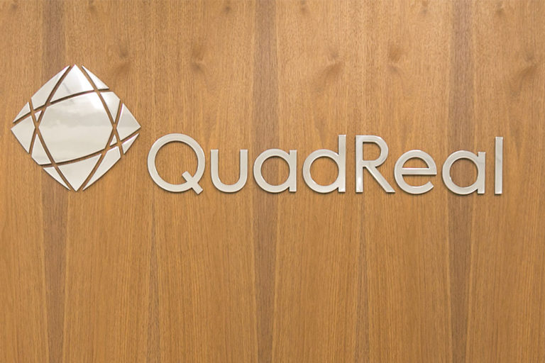 Quadreal metal sign on wood background