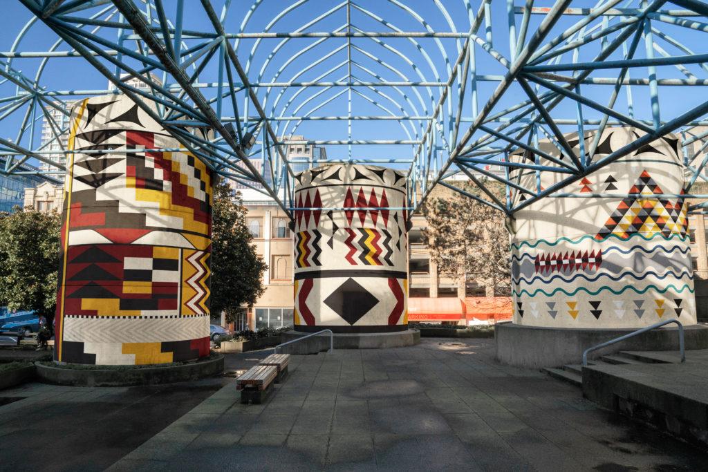 Three pillars with Coast Salish weaving mural designs