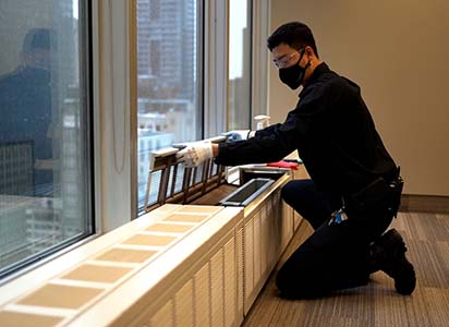Building operator cleaning air vents